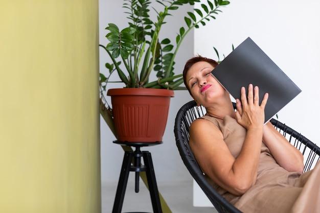Vrij volwassen dame met tijdschrift poseren