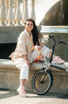 Vrij volwassen vrouw poseren met milieuvriendelijke fiets