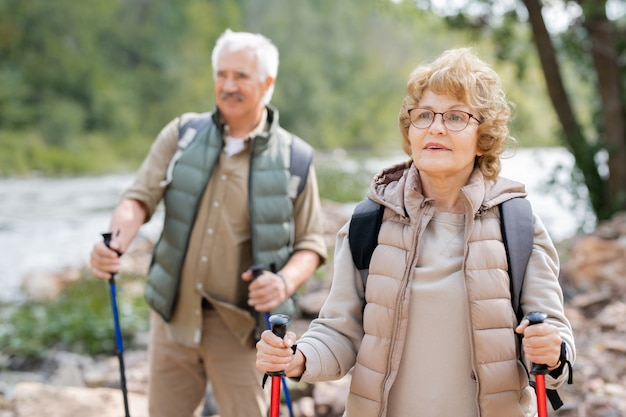 Vrij volwassen vrouwelijke wandelaar met wandelstokken en haar echtgenoot die langs rivieroever beweegt terwijl het chillen