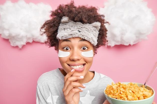 Vrij vrolijk afro-amerikaans meisje kijkt vrolijk naar de voorkant glimlacht toothily houdt kom cornflakes en lepel draagt blinddoek en slaappak heeft heide ontbijt staat binnen met wolken boven