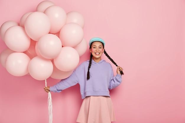 Vrij vrolijk aziatisch tienermeisje komt op vakantie met een bos luchtballonnen, heeft twee donkere lange vlechten, rode wangen en minimale make-up, draagt een oversized paarse trui en rok, in een goed humeur