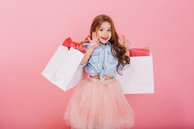 Vrij vrolijk jong meisje in tule rok, met lang donkerbruin haar wandelen met witte pakketten op roze achtergrond. mooie zoete momenten van kleine prinses, best vriendelijk kind met plezier voor de camera