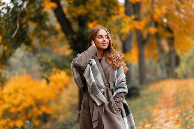 Vrij vrolijk jong vrouwenmodel in een stijlvolle jas met een gebreide vintage sjaal poseren in een bos op een achtergrond van bomen met oranje gebladerte. aantrekkelijk gelukkig meisje ontspant buiten in het park.