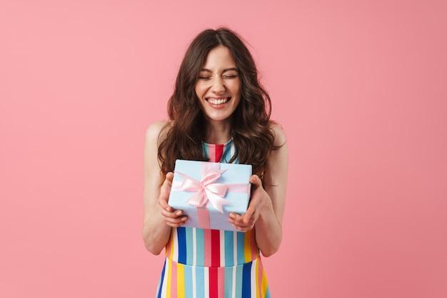 Vrij vrolijk lachende positieve schattige vrouw poseren geïsoleerd over roze muur met huidige geschenkdoos.