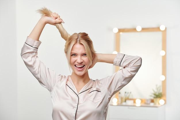 Vrij vrolijk meisje in zijden pyjama's met paardenstaart van haar lange dikke blonde gezonde haar terwijl ze staat