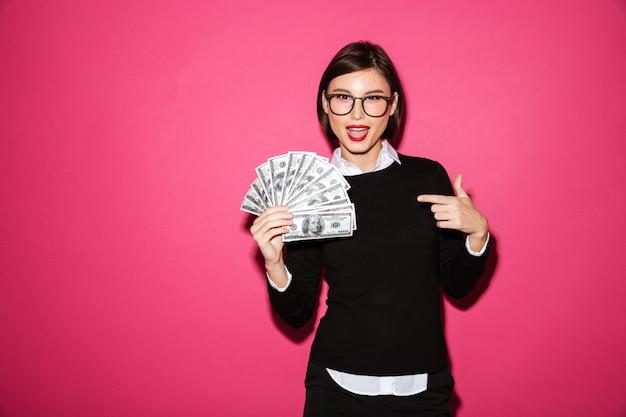 Vrij vrolijke dame die op geïsoleerd geld richt
