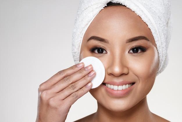 Vrij vrolijke dame met handdoek op hoofd die haar gezicht schoonmaakt