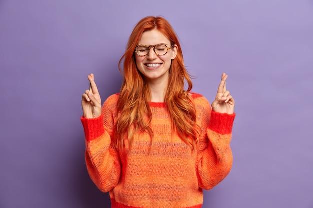 Vrij vrolijke gember vrouw staat met gekruiste vingers doet wens en sluit ogen gekleed in casual trui.