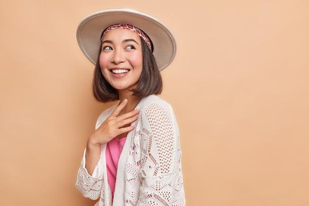 Vrij vrolijke jonge aziatische vrouw met een brede glimlach staart vrolijk weg en draagt een hoed met een witte gebreide jas staat zijwaarts geïsoleerd over een beige muur