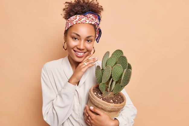 Vrij vrolijke jonge vrouw raakt gezicht zachtjes vast houdt pot sappige groene cactus glimlacht aangenaam toont witte tanden draagt modieuze kleding geïsoleerd over beige muur