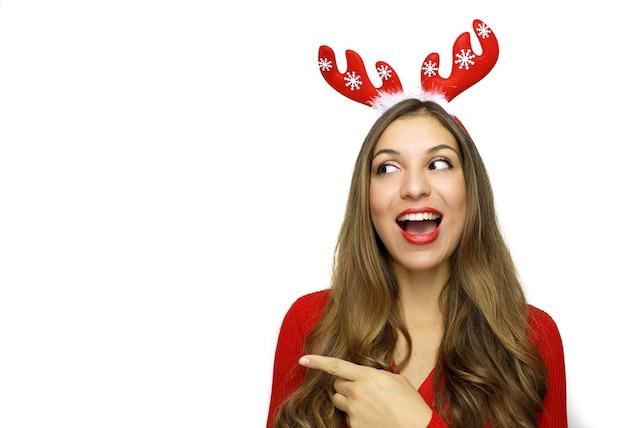 Vrij vrolijke kerstmisvrouw die met vinger gebaart en naar de kant kijkt
