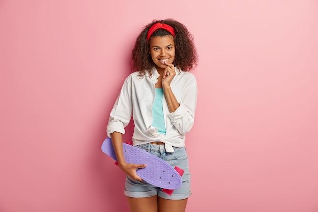 Vrij vrolijke meisjesskater die tijdens het zomerweekend naar skatepark gaat
