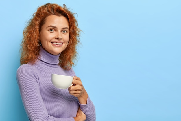 Vrij vrolijke vrouw met gemberhaar staat half naar de camera gedraaid met een witte mok koffie of thee