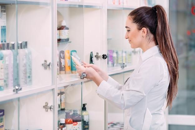 Vrij vrouwelijke apotheker die producten van lichaamsverzorging in apotheek aanbiedt.