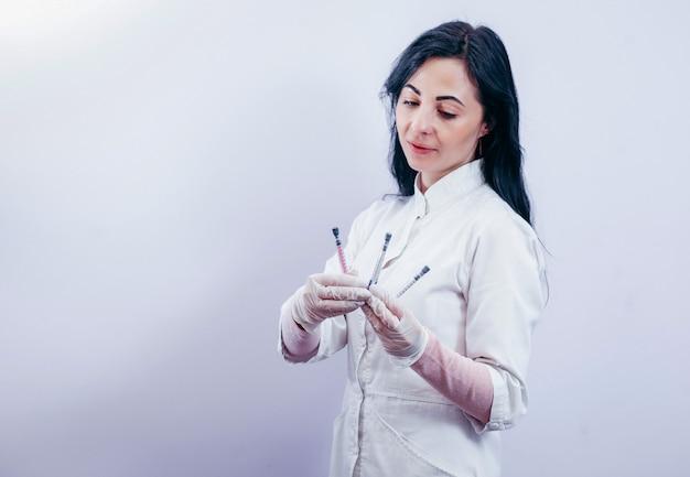 Vrij vrouwelijke arts die witte medische mantel draagt en spuit op grijze ruimte houdt