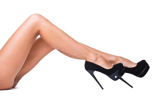 Vrij vrouwelijke benen met zwarte hoge hakken geïsoleerd op een witte achtergrond