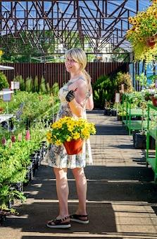 Vrij vrouwelijke bloemist werkt met bloemen in een tuincentrum.