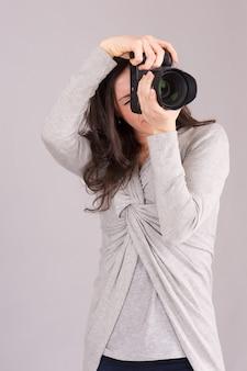 Vrij vrouwelijke fotograaf die in studio werkt