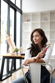 Vrij vrouwelijke kunstenaar zit in het kunstatelier.