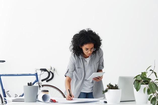 Vrij vrouwelijke ontwerpmedewerker die volumineus donker haar heeft dat een casual overhemd draagt
