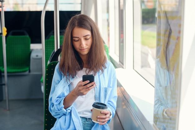 Vrij vrouwelijke passagier zit met smartp hone tijdens het verplaatsen in de moderne tram of metro. reis met het openbaar vervoer.