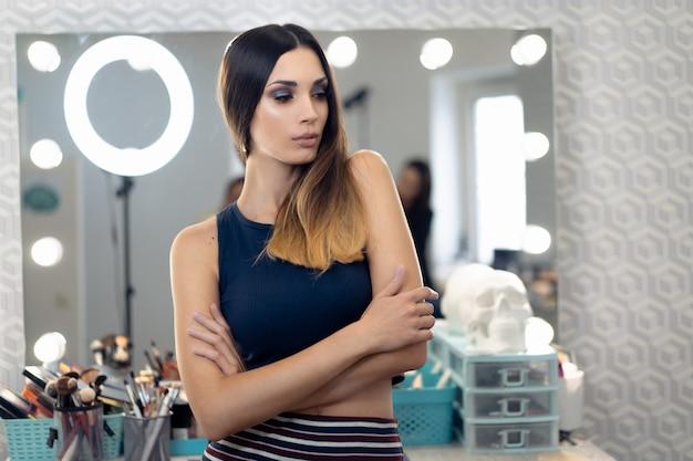 Vrij vrouwelijke schoonheidsspecialist staande poseren bij haar en schoonheidssalon
