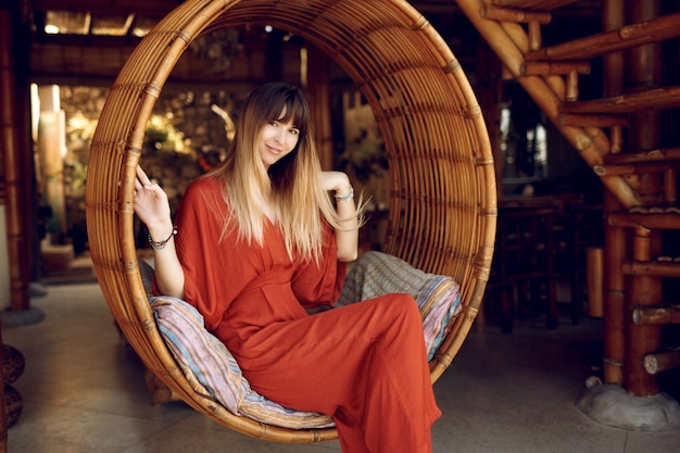 Vrij vrouwelijke situering in hangende bamboetrap op openluchtveranda van houten bungalow