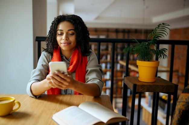 Vrij vrouwelijke student houdt telefoon in bibliotheekcafé. vrouw die een onderwerp, onderwijs en kennis leert. meisje studeert in campuscafetaria