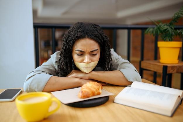 Vrij vrouwelijke student met haar mond dicht geplakt kijken op croissant in bibliotheekcafé. vrouw die een onderwerp, onderwijs en kennis leert. meisje studeert in campuscafetaria