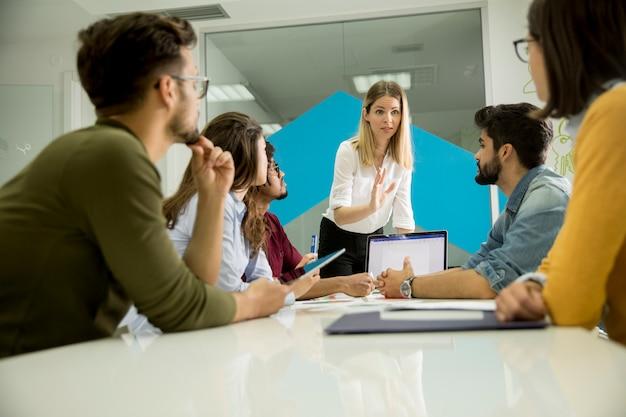 Vrij vrouwelijke teamleider die met gemengde rasgroep mensen spreken in het bureau