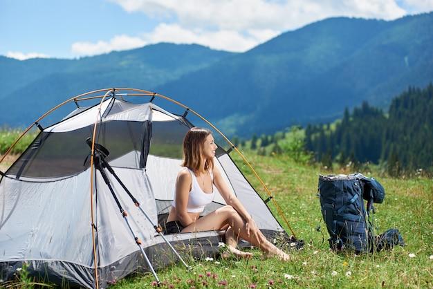 Vrij vrouwelijke wandelaarzitting bij tentingang naast rugzak en trekkingstokken