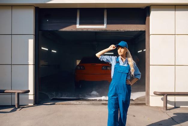 Vrij vrouwelijke wasmachine in uniform, autowasdienst.