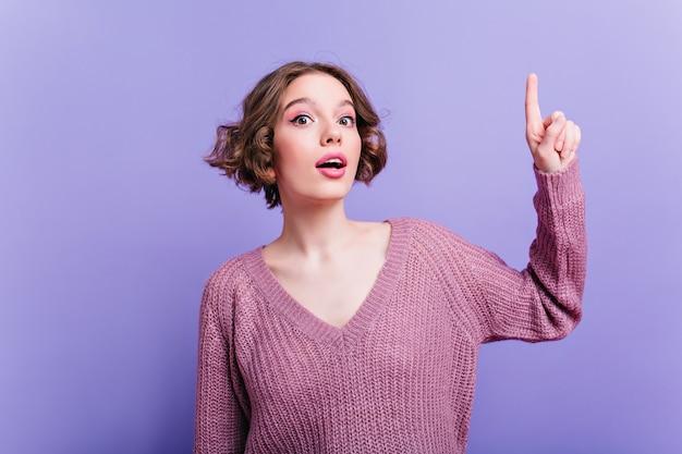 Vrij wit meisje met lichte make-up heeft een idee. nieuwsgierige jonge vrouw in gebreide kleding poseren met vinger omhoog.