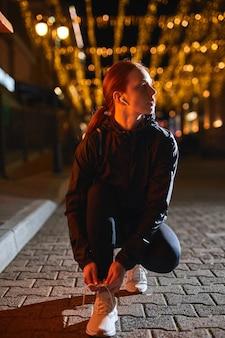 Vrij zelfverzekerde hardloper vrouw in sportieve kleding bereidt zich voor op jogging stropdas schoenveters portret van yo...