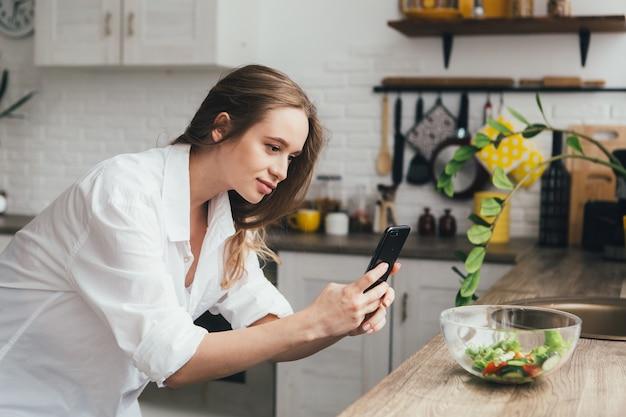 Vrij zwanger meisje maakt foto's van een bereide salade op haar smartphone