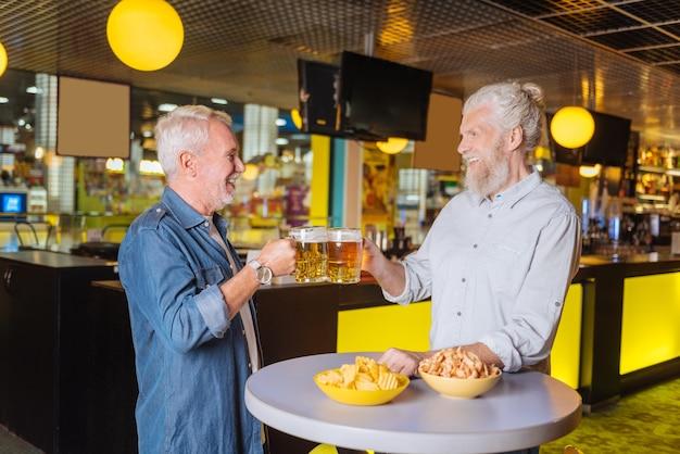 Vrijdag avond. blije gelukkige mannen die bier drinken tijdens een ontmoeting in de kroeg