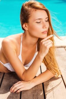 Vrije dag bij het zwembad. mooie jonge vrouw in witte bikini die bij het zwembad ligt en de ogen gesloten houdt