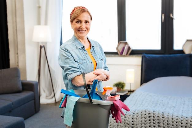Vrije dag doorbrengen. opwindende hardwerkende vrouw wordt voorbereid op massale schoonmaak en het verzamelen van gereedschappen en producten