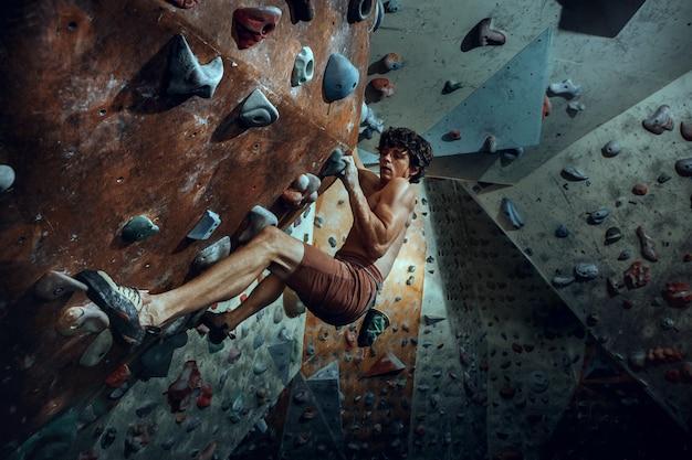 Vrije klimmer die kunstmatige rots binnen beklimt