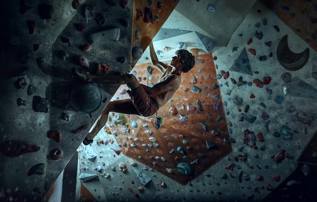 Vrije klimmer jonge mens die kunstmatige kei binnen beklimt