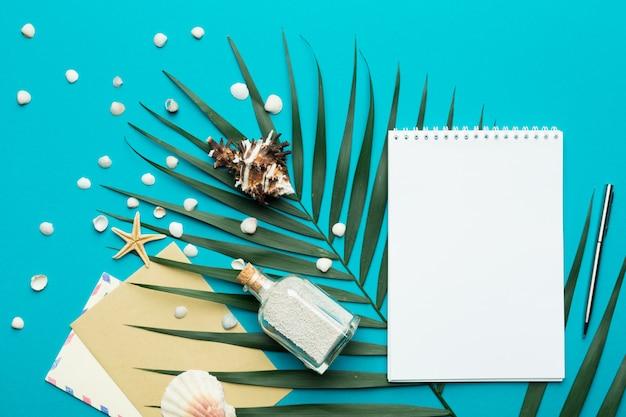 Vrije tijd concept. notebook, zand in een fles en schelpen op een heldere papier achtergrond.