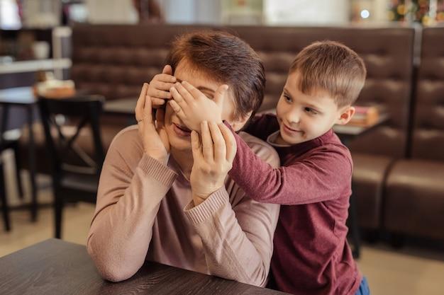 Vrije tijd en amusement voor gezinnen. gelukkige oma met kort haar, een bril en een kleinzoon rusten in een café. kind omhelst grootmoeder en sluit haar ogen met haar eigen handen
