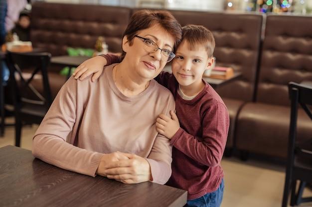 Vrije tijd en amusement voor gezinnen. gelukkige oma met kort haar, een bril en een kleinzoon rusten in een café. kind omhelst grootmoeder