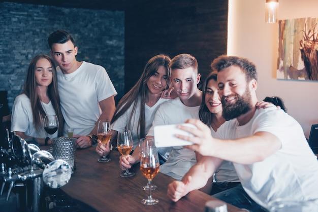 Vrije tijd en communicatieconcept. groep gelukkig lachende vrienden genieten van drankjes en praten in de bar of pub