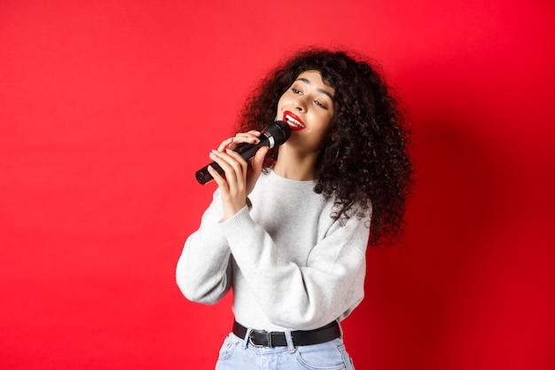 Vrije tijd en hobby's concept. stijlvolle jonge vrouw karaoke zingen, opzij kijken en microfoon vasthouden, lied uitvoeren, staande op rode achtergrond.