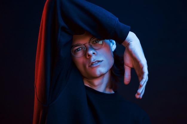 Vrije tijd hebben. studio opname in donkere studio met neonlicht. portret van ernstige man