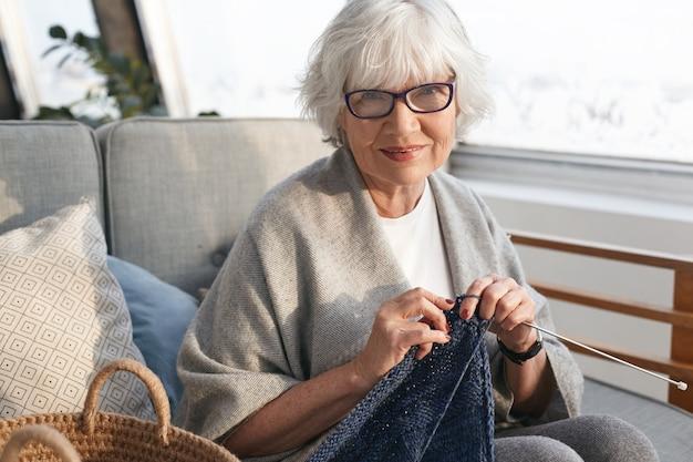 Vrije tijd, hobby, ontspanning, leeftijd en handwerkconcept. vrolijke charmante vrouw van middelbare leeftijd met pensioen thuis ontspannen, warme trui breien te koop, stijlvolle bril dragen en glimlachen