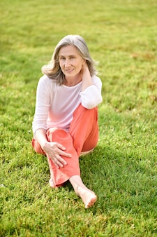Vrije tijd in de natuur. vrouw van pensioengerechtigde leeftijd in blouse en broek met blote voeten zittend op het gazon in een goed humeur op zomerdag