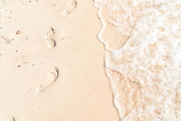 Vrije tijd in de zomer - voetafdrukken op zand met zee golf. vintage kleur effect.