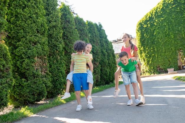 Vrije tijd. jongere jongens en meisjes in lichte, comfortabele kleding die op zonnige dag samen actieve vrije tijd in het park doorbrengen